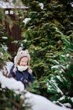 Nettes Kindermädchen in der Eulenstrickmütze auf dem Weg im schneebedeckten Garten des Winters Stockfotos