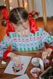 Nettes Kindermädchen in der Saisonstrickjacke, die zu Hause Weihnachtspostkarten macht Lizenzfreie Stockfotos