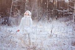 Nettes Kindermädchen in der weißen Ausstattung auf dem Weg in Winter gefrorenem Wald Stockbilder
