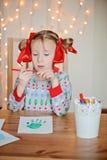 Nettes Kindermädchen in der Weihnachtsstrickjacke, die handprints Postkarte macht Stockbilder