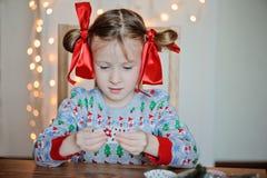 Nettes Kindermädchen in der Weihnachtsstrickjacke, die Postkarten macht Stockfoto