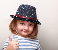 Nettes Kindermädchen im blauen Hut, der sich Daumen zeigt Lizenzfreies Stockfoto