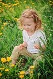 Nettes Kindermädchen im Löwenzahnkranz auf Frühlingsblumenfeld Stockbild