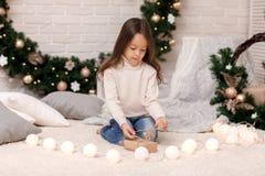 Nettes Kindermädchen verpackende Weihnachtsgeschenke zu Hause lizenzfreie stockbilder