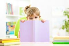 Nettes Kindermädchen, das hinter Buch sich versteckt Lizenzfreies Stockbild