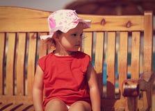 Nettes Kindermädchen im Hut, der auf der Bank auf dem Strand sitzt Lizenzfreie Stockbilder