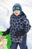 Nettes Kinderrodeln Kleinkindjunge, der einen Schlitten im Schnee reitet lizenzfreies stockfoto