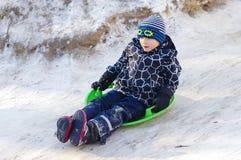Nettes Kinderrodeln Kleinkindjunge, der einen Schlitten im Schnee reitet lizenzfreie stockfotos