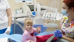 Nettes Kinderwellenartig bewegende Hand beim Sitzen auf zahnmedizinischem Stuhl nahe bei Doktor in den Gummihandschuhen und mediz stock video footage