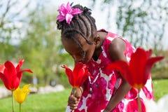 Nettes kleines afrikanisches Mädchen, das im Garten spielt stockfotos