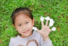Nettes kleines asiatisches Kindermädchen, das auf Rasen des grünen Grases mit leeren weißen Aufklebern der Vertretung auf ihren F stockfotografie