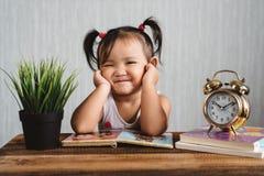 Nettes kleines asiatisches lustiges Gesicht machendes oder lächelndes Babykleinkind während Lesebücher mit Wecker stockfotografie