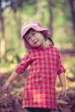 Nettes kleines asiatisches Mädchen, das im schönen Herbst im Freien spielt Stockbild