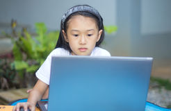 Nettes kleines asiatisches Mädchen, das Laptop verwendet stockfoto