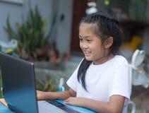 Nettes kleines asiatisches Mädchen, das Laptop verwendet lizenzfreies stockfoto