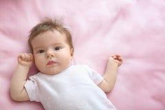 Nettes kleines Baby, das auf Bett liegt Stockfotos