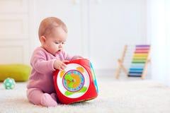 Nettes kleines Baby, das auf dem Teppich unter den bunten Spielwaren sitzt Stockfotografie