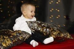 Nettes kleines Baby, das am Fenster sitzt und weg schaut Raum verziert auf Weihnachten lizenzfreie stockfotos