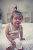Nettes kleines Baby, das im Bettlächeln sitzt Stockbild