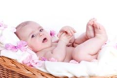 Nettes kleines Baby, das im Korb liegt Lizenzfreies Stockfoto