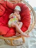 Nettes kleines Baby, das im Lehnsessel auf dem Strand sich entspannt stockbild