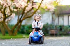 Nettes kleines Baby, das mit blauem kleinem Spielzeugauto im Garten des Hauses oder der Kindertagesstätte spielt Entzückendes sch lizenzfreies stockbild