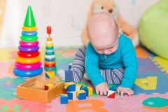 Nettes kleines Baby, das mit bunten Spielwaren spielt Lizenzfreies Stockfoto