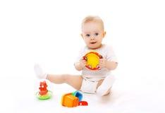 Nettes kleines Baby, das mit Spielwaren auf Weiß spielt Stockfoto