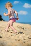 Nettes kleines Baby, das am Ozeanstrand läuft Stockbild