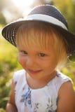 Nettes kleines blondes lächelndes Mädchen in einem blauen Hut Stockfoto