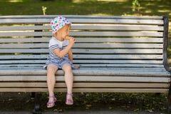 Nettes kleines blondes Mädchen, das auf einer grauen Holzbank in einem Park sitzt, Eiscreme isst und beiseite schaut Stockfotografie