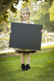 Nettes kleines blondes Mädchen, das draußen eine schwarze Tafel hält Stockfotografie