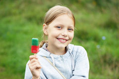 Nettes kleines blondes Mädchen, das Eiscreme isst Stockfotografie