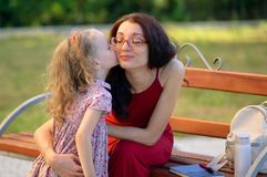 Nettes kleines blondes Mädchen küsst ihre junge Brunette-Mutter in Eyesglasses und in rotem Kleid, die auf der Bank in sitzen Lizenzfreie Stockfotos