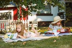 Nettes kleines blondes Mädchen-Lesebuch draußen auf Gras Stockfoto