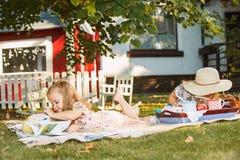 Nettes kleines blondes Mädchen-Lesebuch draußen auf Gras Stockbilder