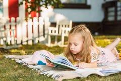 Nettes kleines blondes Mädchen-Lesebuch draußen auf Gras Lizenzfreie Stockbilder