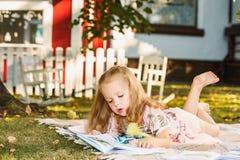 Nettes kleines blondes Mädchen-Lesebuch draußen auf Gras Lizenzfreie Stockfotos