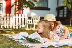 Nettes kleines blondes Mädchen-Lesebuch draußen auf Gras Stockfotografie