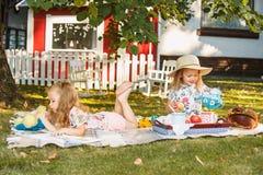 Nettes kleines blondes Mädchen-Lesebuch draußen auf Gras Stockfotos