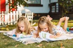 Nettes kleines blondes Mädchen-Lesebuch draußen auf Gras Lizenzfreies Stockbild