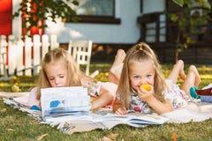 Nettes kleines blondes Mädchen-Lesebuch draußen auf Gras Stockbild
