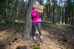 Nettes kleines blondes Mädchen mit dem Weidenkorb, der am Wald aufwirft Stockfotografie