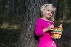 Nettes kleines blondes Mädchen mit dem Weidenkorb, der am Wald aufwirft Stockfoto