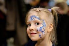 Nettes kleines blondes Mädchen mit Gesichtsmalerei Blaues abstraktes Schneeflockenmuster durch Aquarell auf Kindergesicht Entzück Stockfotos