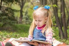 Nettes kleines blondes Mädchen mit zwei Pferdeschwänzen, die mit einem Buch sich entspannen Stockfoto