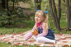 Nettes kleines blondes Mädchen mit zwei Pferdeschwänzen, die mit einem Buch sich entspannen Lizenzfreie Stockbilder
