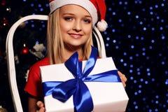 Nettes kleines blondes Mädchen in Sankt-Hut und in rotem Kleid, die eine Geschenkbox auf dem Hintergrund Feiertag glänzenden ligh Lizenzfreie Stockbilder