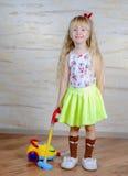 Nettes kleines blondes Mädchen, welches das Haus Staub saugt Lizenzfreies Stockbild