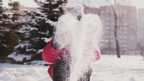 Nettes kleines glückliches europäisches Mädchen im Winter kleidet das Betrachten der Kamera und wirft Schnee in der Luft und in d stock video